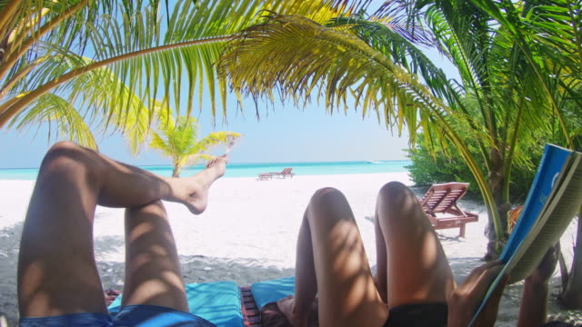 ms couple relaxing under palm trees,reading on idyllic tropical beach,maldives - lounge chair stock videos & royalty-free footage