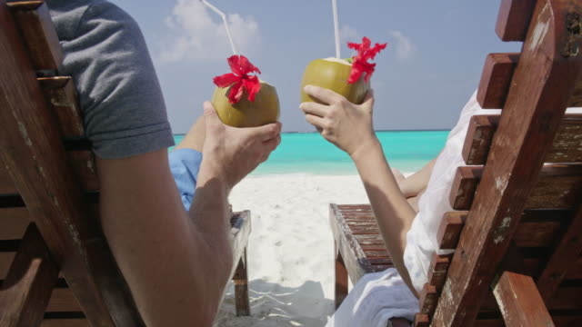 ms couple relaxing,toasting coconut drinks on lounge chairs on sunny tropical ocean beach,maldives - outdoor chair stock videos & royalty-free footage