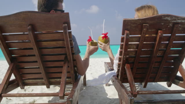 ms couple relaxing,toasting coconut drinks on lounge chairs on sunny tropical ocean beach,maldives - coconut stock videos & royalty-free footage