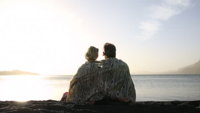 Couple relax/stay warm with sarong at lake edge, sunrise
