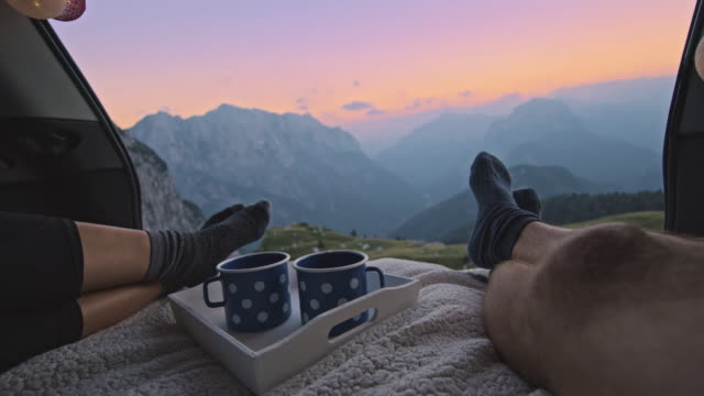 vídeos y material grabado en eventos de stock de slo mo pareja descansando y disfrutando de la vista a la montaña desde el maletero camper - maletero