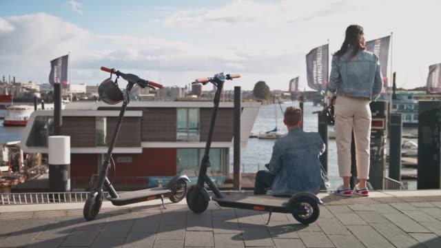 paar ruht sich mit elektrorollern auf der promenade aus - position stock-videos und b-roll-filmmaterial