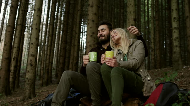 Couple resting in the forest and drinking coffee