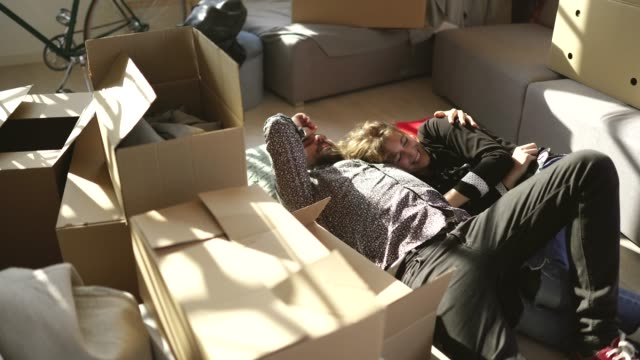 couple resting on floor at new apartment - relocation stock videos & royalty-free footage