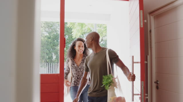 Couple Returning Home From Shopping Trip Carrying Groceries In Plastic Free Bags
