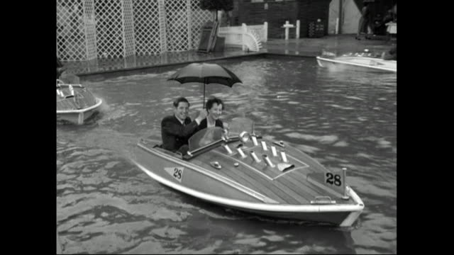 vídeos de stock e filmes b-roll de couple ride in small boat holding umbrella;1951 - etiqueta boas maneiras