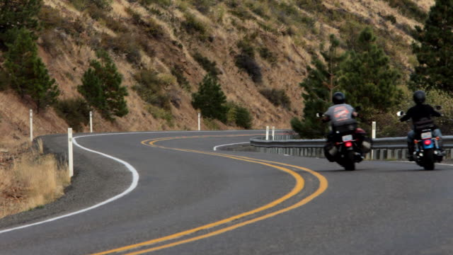 a couple rides two harley davidson motorcycles through an s curve in cle elum, washington. - biegung stock-videos und b-roll-filmmaterial