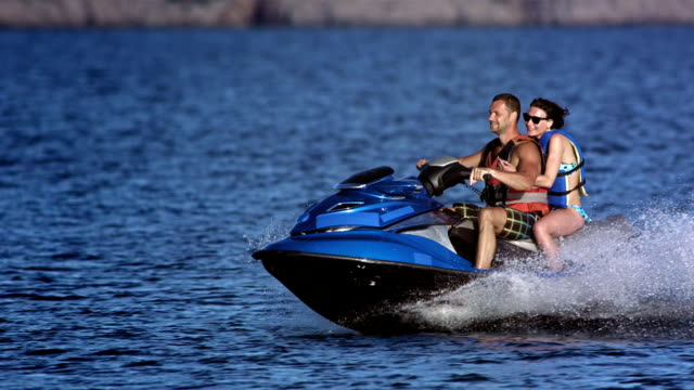 slo mo couple riding a jet boat - jet ski stock videos & royalty-free footage