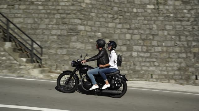 couple riding a motorcycle on a road near a lake - motorcycle stock videos & royalty-free footage