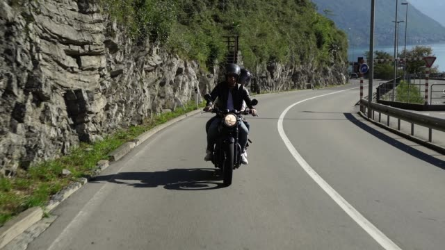 paar mit dem motorrad auf einer straße in der nähe von einem see - jacke stock-videos und b-roll-filmmaterial