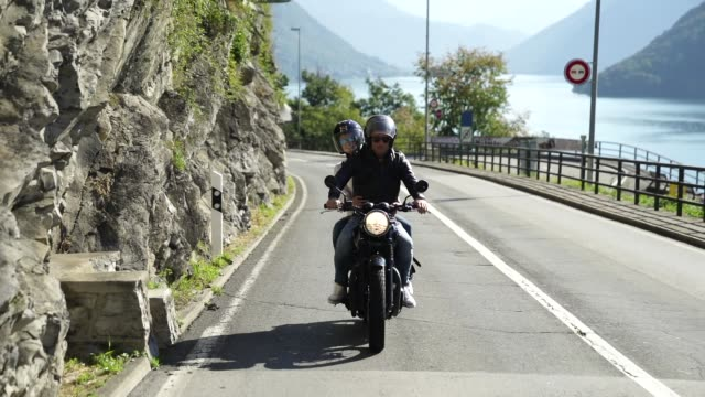 couple riding a motorcycle on a road near a lake - casco da motociclista video stock e b–roll