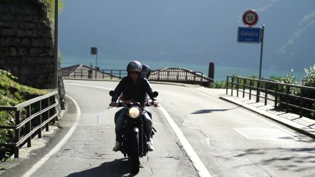 vídeos de stock e filmes b-roll de couple riding a motorcycle on a road near a lake - capacete moto