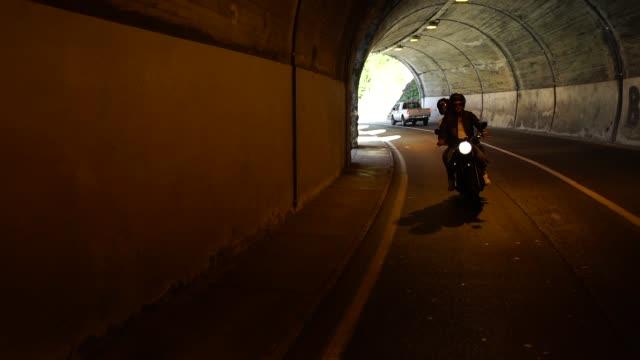 vídeos de stock e filmes b-roll de couple riding a motorcycle on a road near a lake with a tunnel - capacete moto