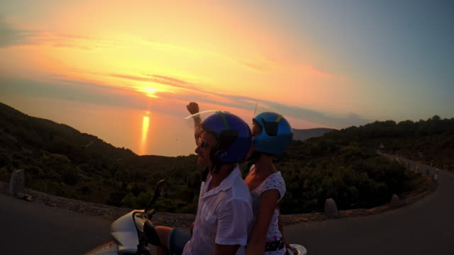 pov couple riding a scooter at dusk - moped stock videos and b-roll footage