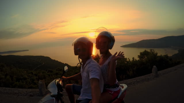 pov couple riding a scooter at sunset - moped stock videos and b-roll footage