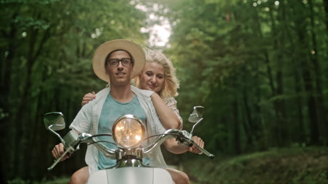 super slo mo couple riding a scooter through a forest - super slow motion stock videos & royalty-free footage
