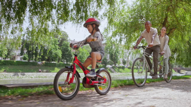 vídeos de stock e filmes b-roll de slo mo ts couple riding a tandem bike and their young daughter is riding beside them through the park - parque público