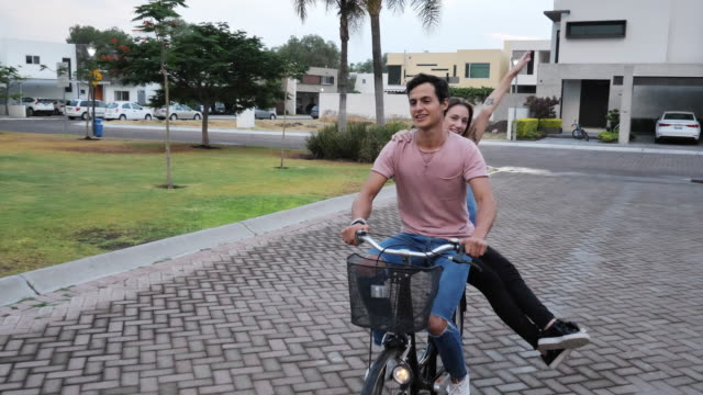 vídeos de stock e filmes b-roll de couple riding bicycle and sharing emotions - casal jovem