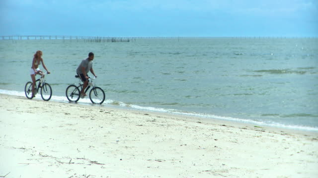 ms pan couple riding bicycles along beach, eastville, virginia, usa - eastville stock videos and b-roll footage