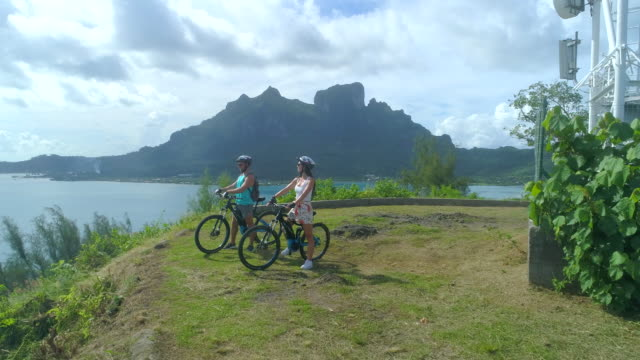 vídeos de stock, filmes e b-roll de a couple riding bicycles in bora bora tropical island. - polinésia francesa