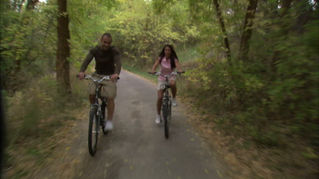 vidéos et rushes de ws rear pov couple riding bikes in woods / provo, utah, usa - provo