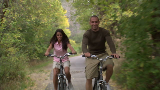 vidéos et rushes de ms rear pov couple riding bikes in woods / provo, utah, usa - provo