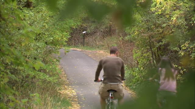 vídeos de stock e filmes b-roll de ws couple riding bikes in woods / provo, utah, usa - provo