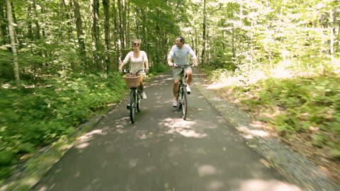 rear pov couple riding bikes on paved path through woods / stowe, vermont, united states - vermont stock videos & royalty-free footage