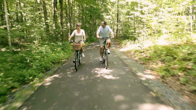 rear pov couple riding bikes on paved path through woods / stowe, vermont, united states - vermont stock-videos und b-roll-filmmaterial
