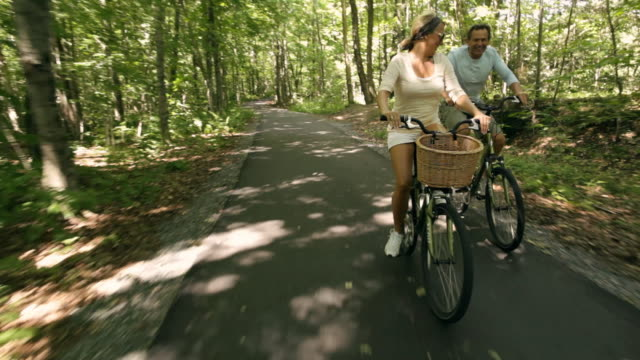 rear pov couple riding bikes on paved path through woods / stowe, vermont, united states - stowe vermont stock videos & royalty-free footage