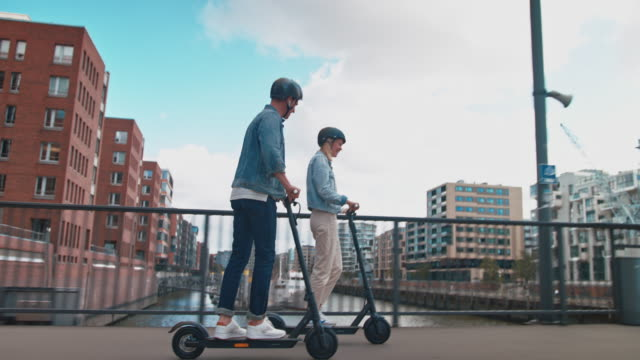 couple riding electric push scooters on bridge - helmet stock videos & royalty-free footage