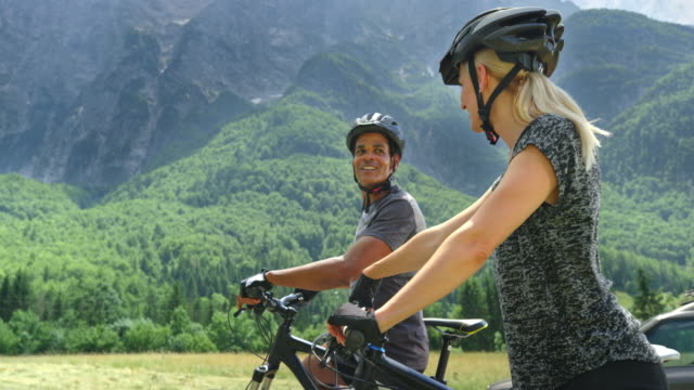 cs couple riding off on their bikes up a mountain valley - harmony stock videos & royalty-free footage