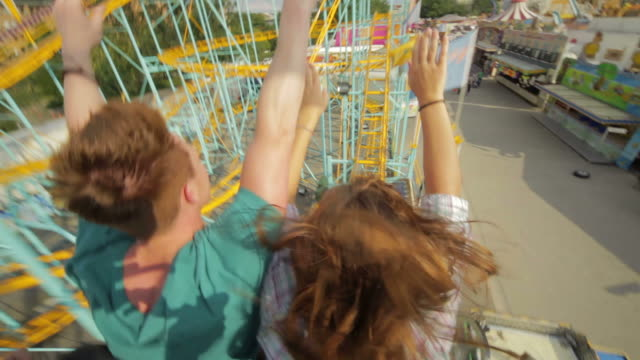 couple riding rollercoaster - rollercoaster stock videos & royalty-free footage
