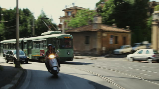 WS REAR POV Couple riding scooter down city street / Rome, Italy