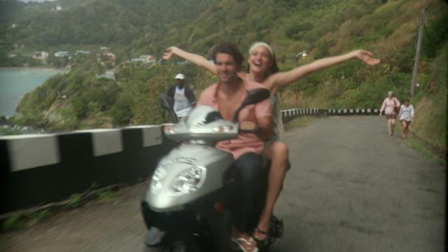 ws pov couple riding scooter / scarborough, tobago, trinidad and tobago  - scooter stock videos & royalty-free footage
