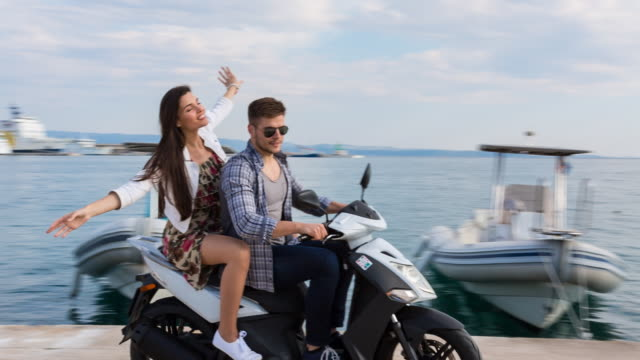 ms couple riding scooter through yacht harbor - young couple stock videos & royalty-free footage
