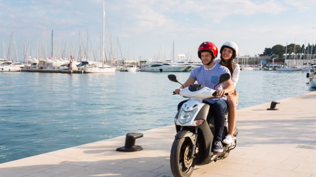 MS couple riding scooter through yacht harbor