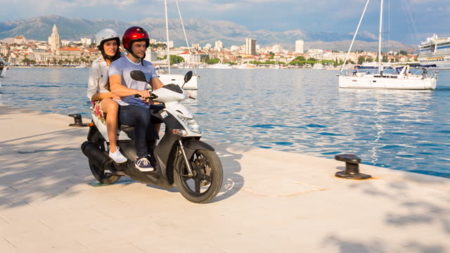 WS couple riding scooter through yacht harbor