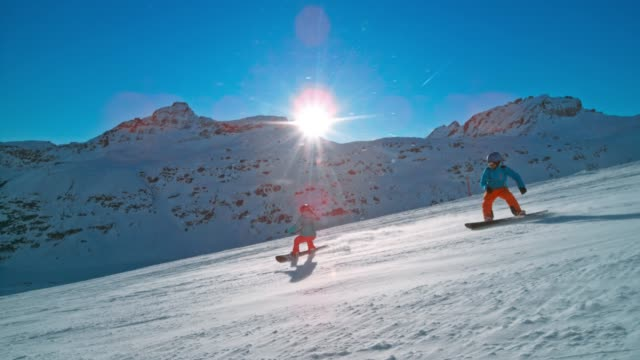 slo mo ts couple riding snowboards down the sunny mountain slope - snowboarding stock videos & royalty-free footage