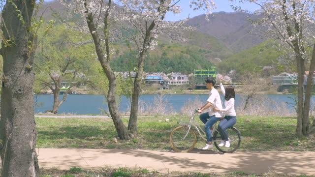 A couple riding the bicycle along the riverside