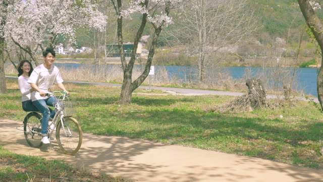 A couple riding the bicycle under cherry blossom trees