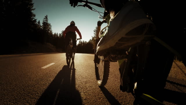 POV Couple riding their bikes on a country road at sunset