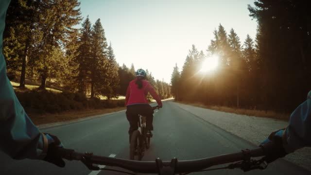 pov 女性の後ろから田舎の道を自転車に乗るバイカー - クロスカントリーサイクリング点の映像素材/bロール