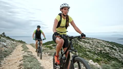 vidéos et rushes de couple à leur vélo sur une montagne à la mer sur une journée nuageuse - faire du vélo tout terrain