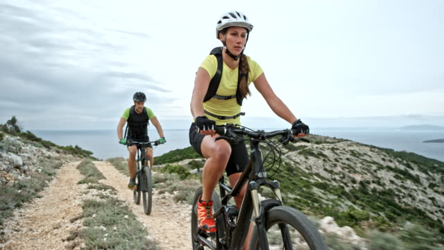 couple riding their bikes up a mountain at the seaside on a cloudy day - mountain biking stock videos & royalty-free footage