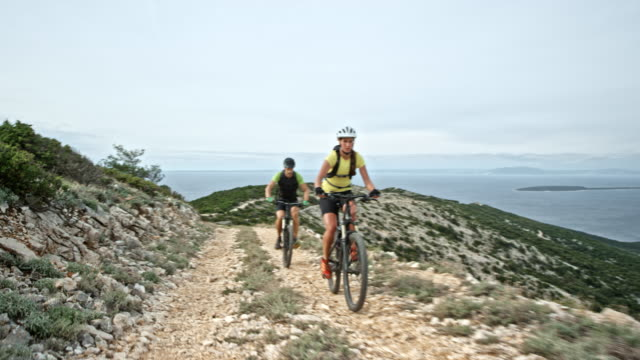 Couple riding their bikes up a mountain on a gravel road above the sea
