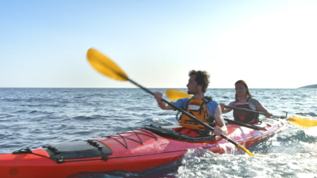 couple riding their kayak at sea in sunshine - quarantenne video stock e b–roll