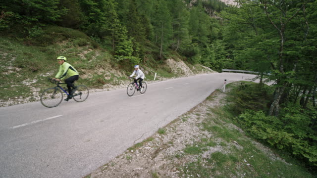 cs couple riding their road bikes up a mountain road - racing bicycle stock videos and b-roll footage