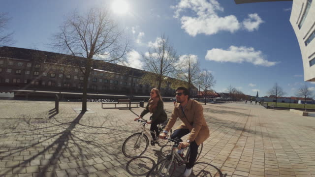 couple riding urban road city bicycles - copenhagen stock videos and b-roll footage