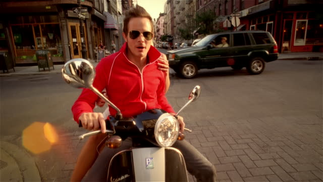 couple riding vespa coming to stop in front of camera / talking to camera - 2006 stock videos & royalty-free footage